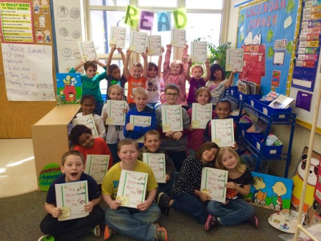 Students in classroom holding up books they made