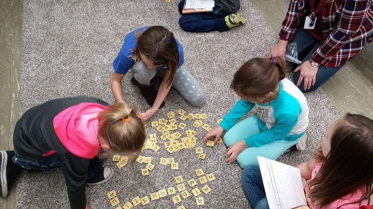 Students playing a word game sitting on the floor