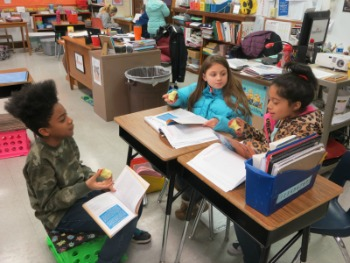 3 Students reading at desks