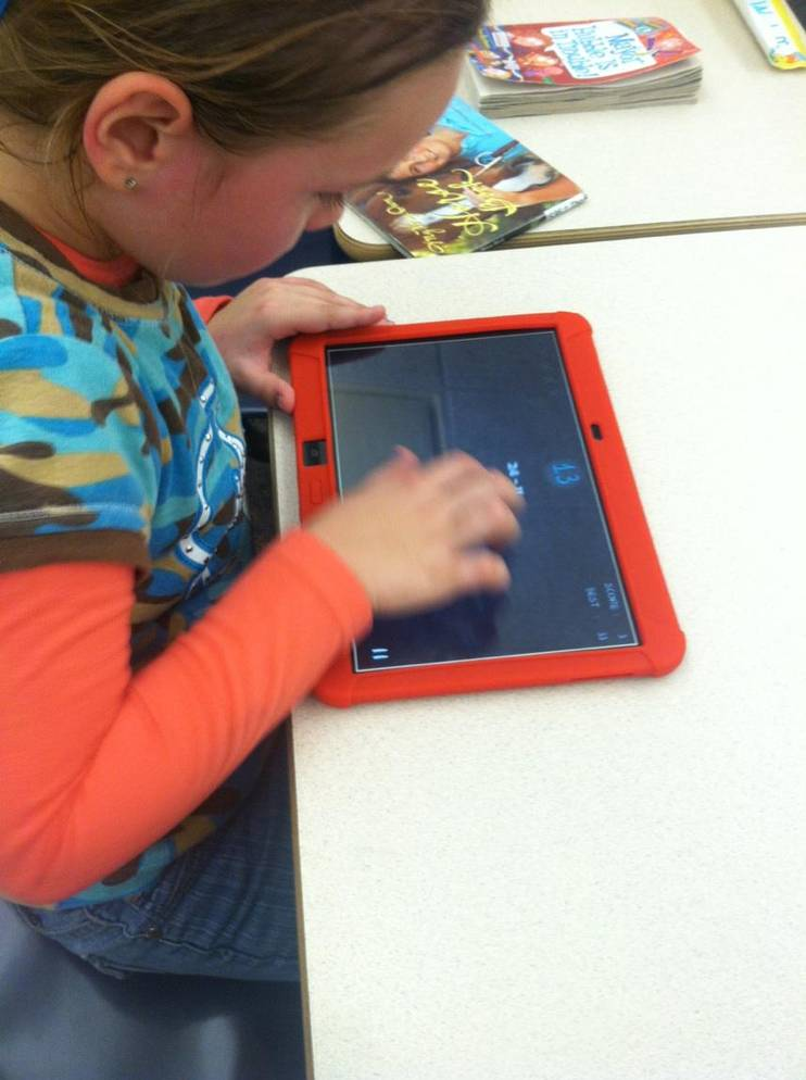 student plays educational tablet game