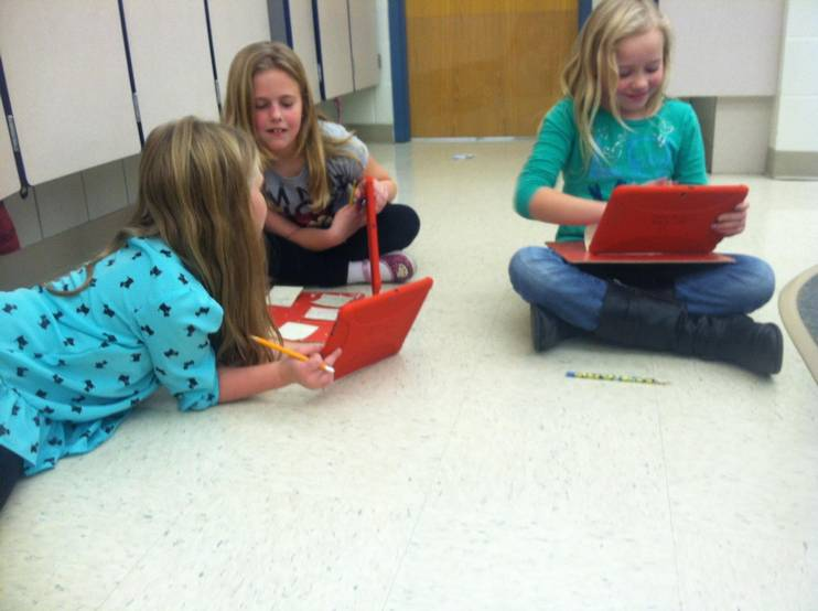 Students collaborate using tablets