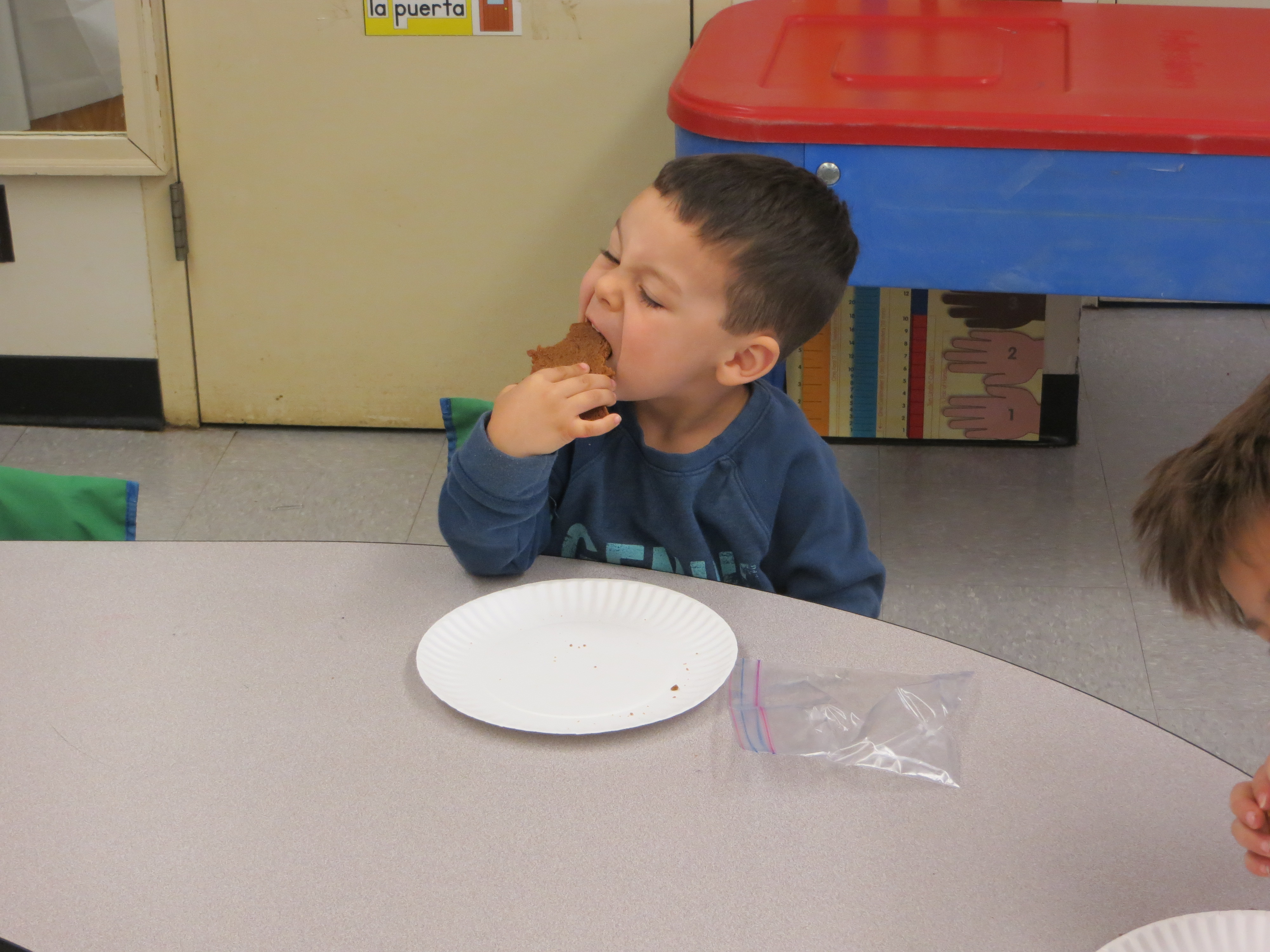 A preschool student enjoys his cookie.