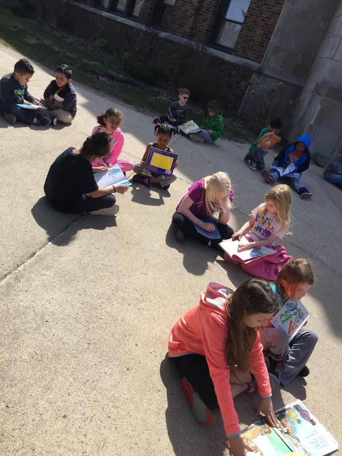 Group of students reading books outside