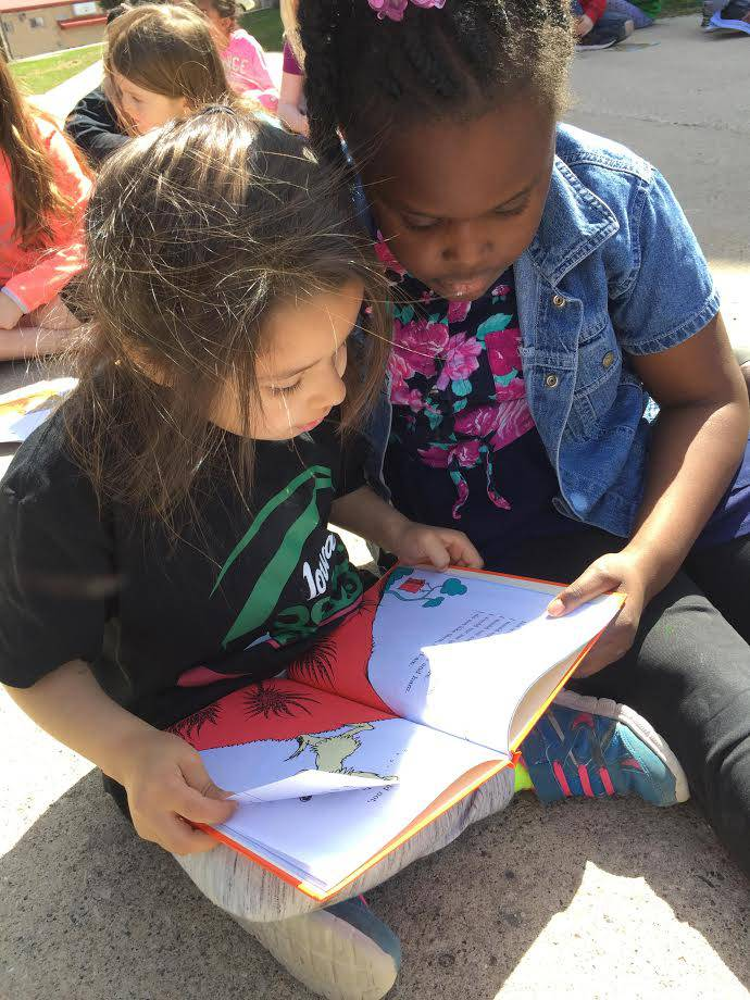 Two students reading a book outside